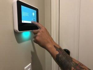 Un técnico da instrucciones sobre cómo programar el panel de seguridad del hogar en una casa inteligente.
