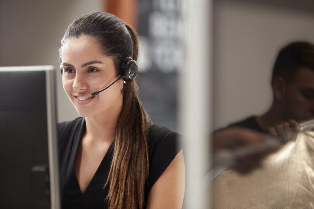 Agente de servicio al cliente femenino trabajando en el escritorio en el centro de llamadas