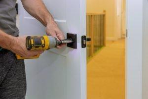 Todos los servicios de un operario instalando la cerradura de la puerta en la habitación con destornillador