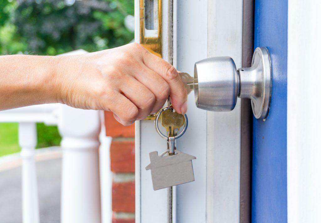 propietario de la casa con una llave abre la puerta